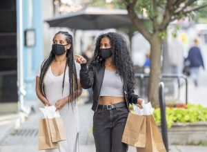 Two woman walking downtown, holding shopping bags, and doing some window shopping while wearing protective face masks during phase 2 of reopening during the COVID-19 pandemic.