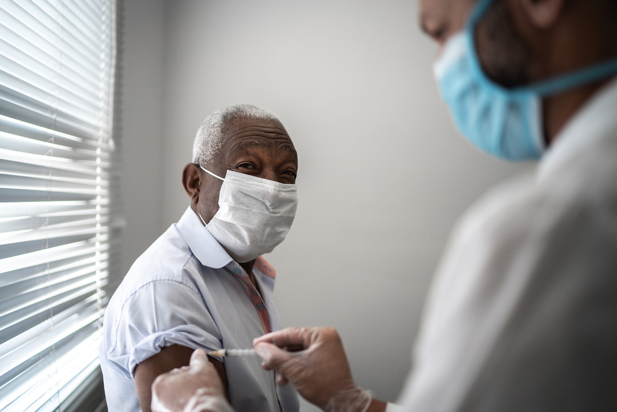 Nurse applying vaccine on patient's arm while wearing a face mask