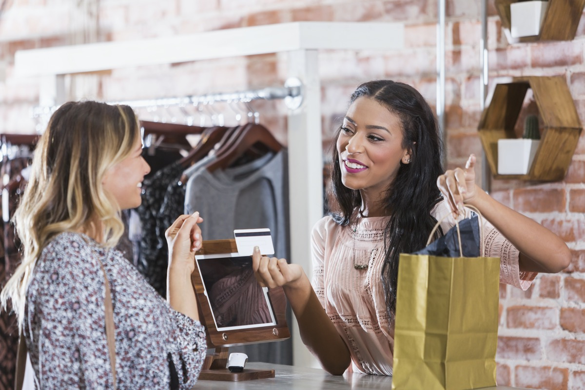 African-American sales associate giving a card and a bag to Caucasian customer