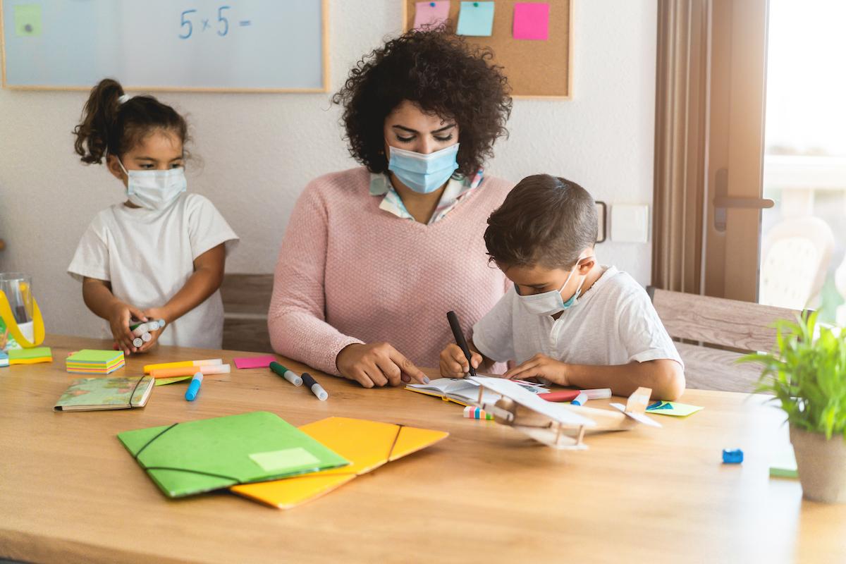 child care provider helping two young children with an art project during coronavirus pandemic; all three are wearing masks