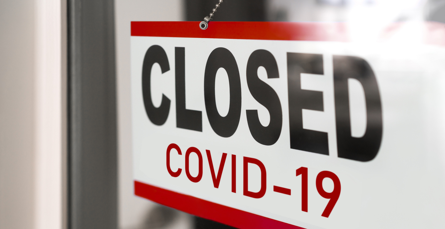A sign hanging on a businesses door telling customers they are closed due to COVID-19