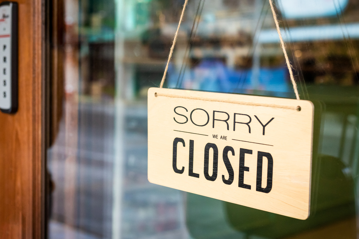 """A sign reading """"sorry we are closed"""" hangs in the window of a shop"""