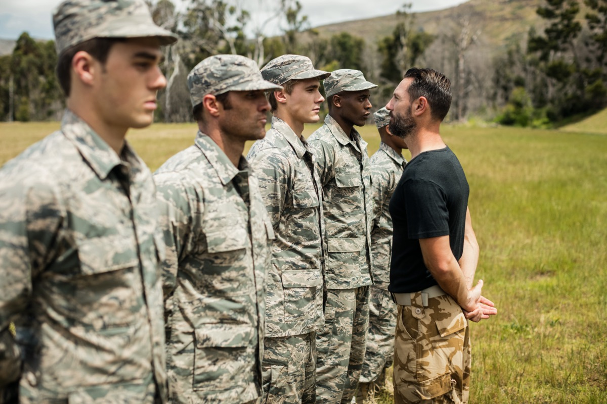 five military men standing in a line and a military officer looking at one of them in the eye during combat training