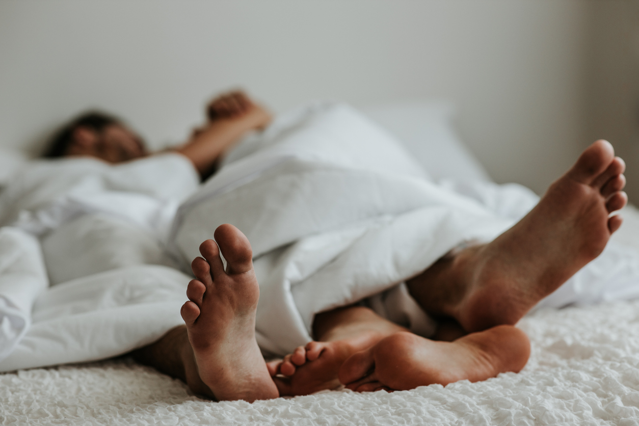 A couple's feet next to each other in bed.