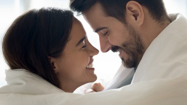 happy couple wrapped in duvet, smiling at each other