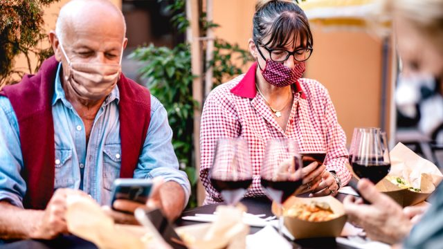 seniors at restaurant, wearing masks, having wine, and looking at their phones