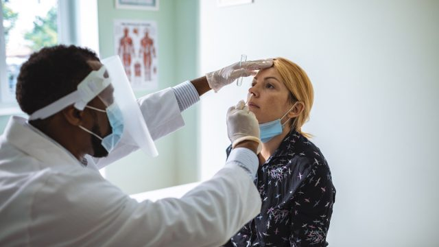 Close up of a young woman having a nasal swab test done by his doctor