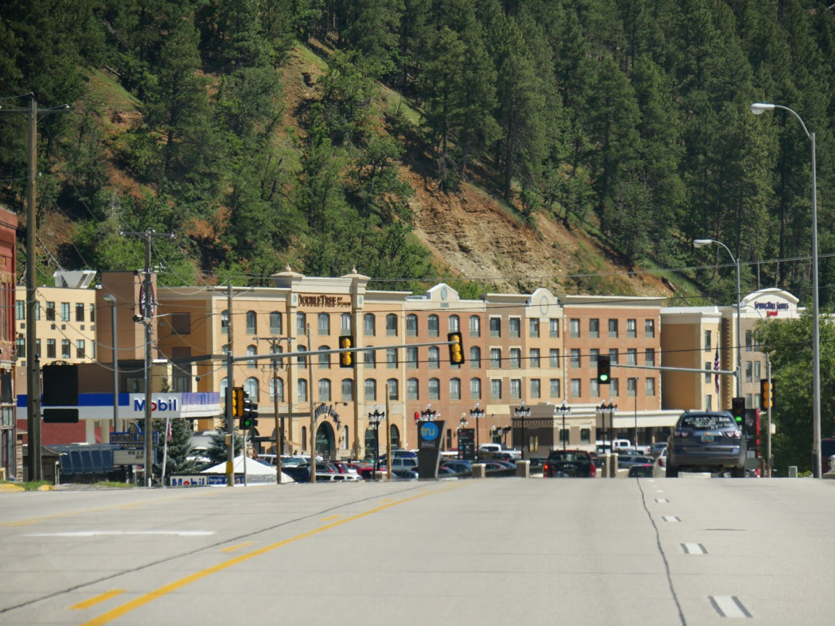 cityscape photo of shops, trees along mountains, and a road in Deadwood City, South Dakota