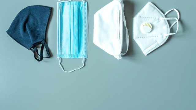 Four different types of face masks resting on a blue background, including a cloth mask, a disposable surgical mask, a cone mask, and a mask with a respirator