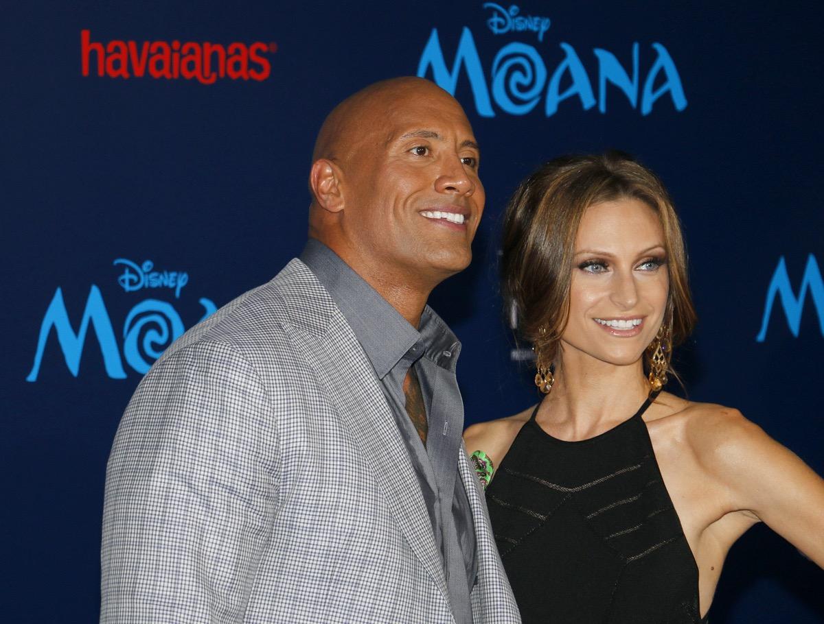 Dwayne Johnson wears a grey suits and Lauren Hashian wears a black dress at the premiere of 'Moana' in 2016
