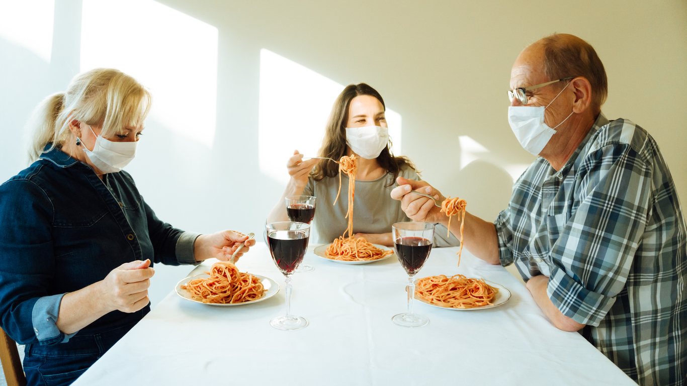 Three family members sit together while eating spaghetti and wearing face masks.