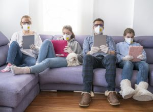 A mother, father, and their two daughters sit on a couch using tablets and devices while wearing face masks.