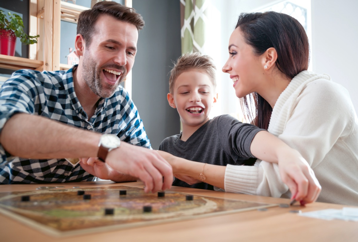 mother, father, and son smiling while playing a board game