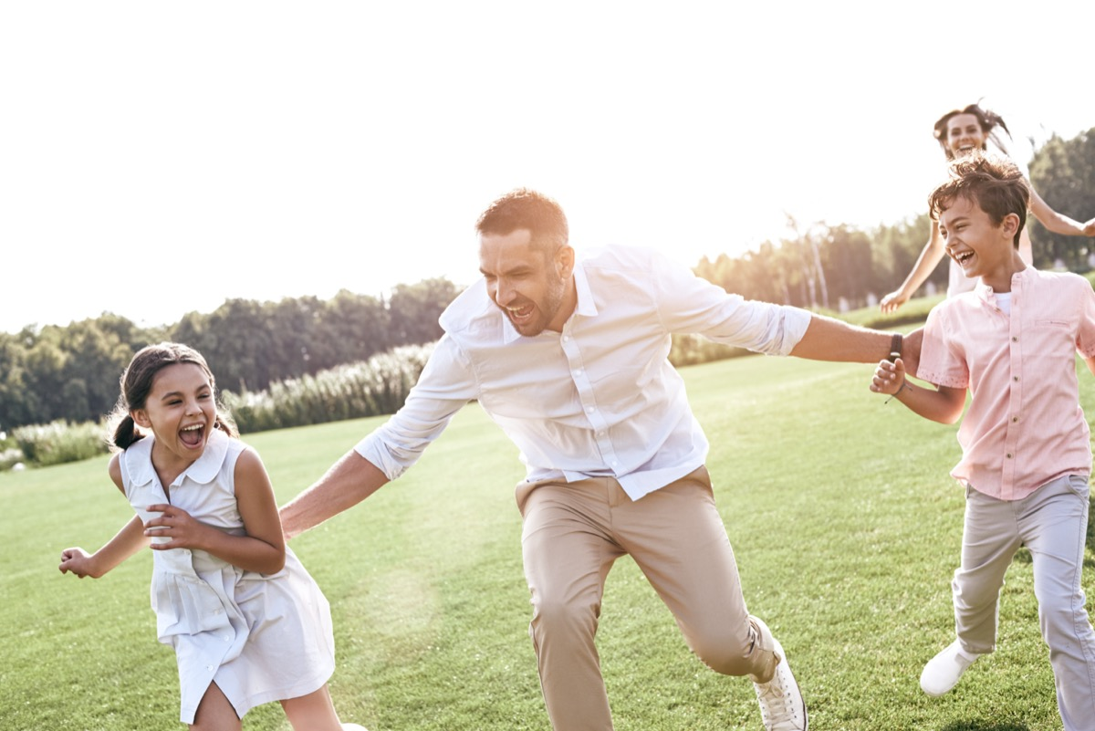a father running through field with son and daughter next to him and his wife running behind them