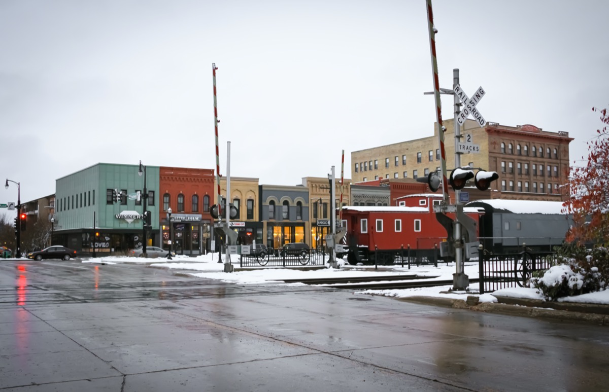 cityscape photo of shop, railroad track, and train in downtown Fargo, North Dakota in the snow