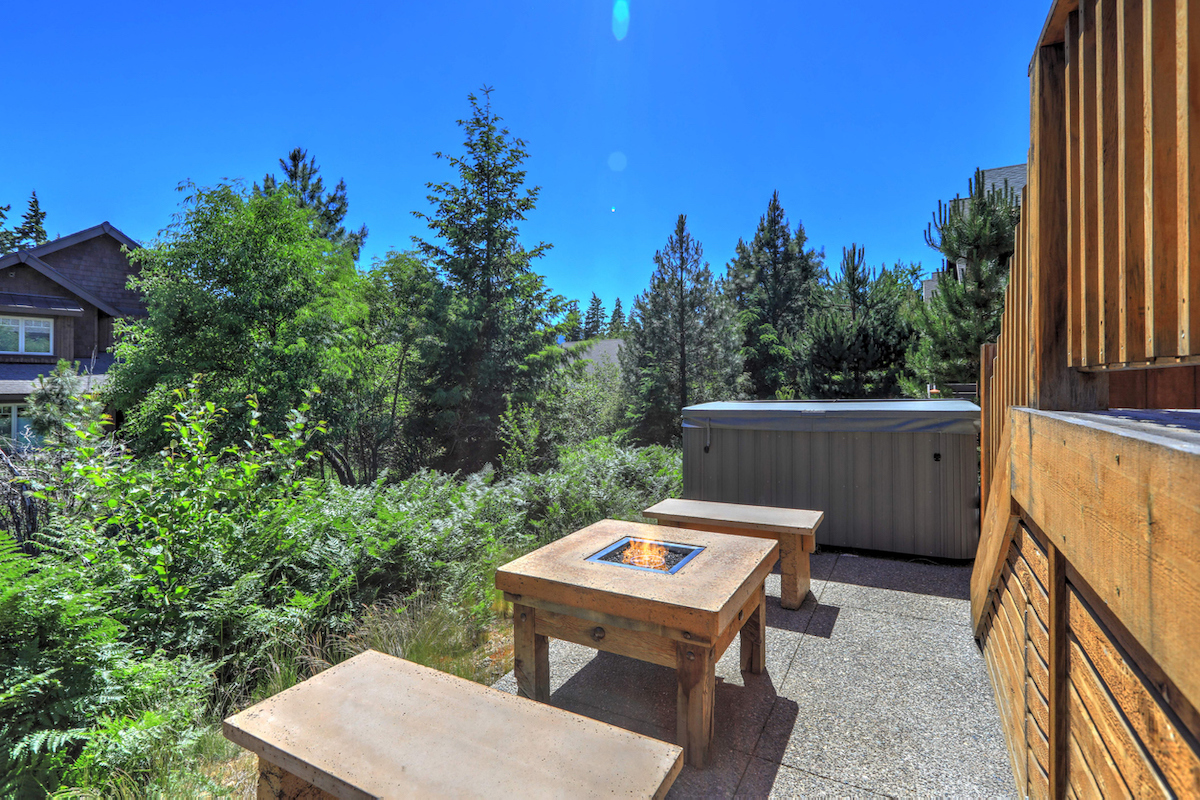 Small but open to greenery back yard space with fire pit table and hot tub and wooden deck