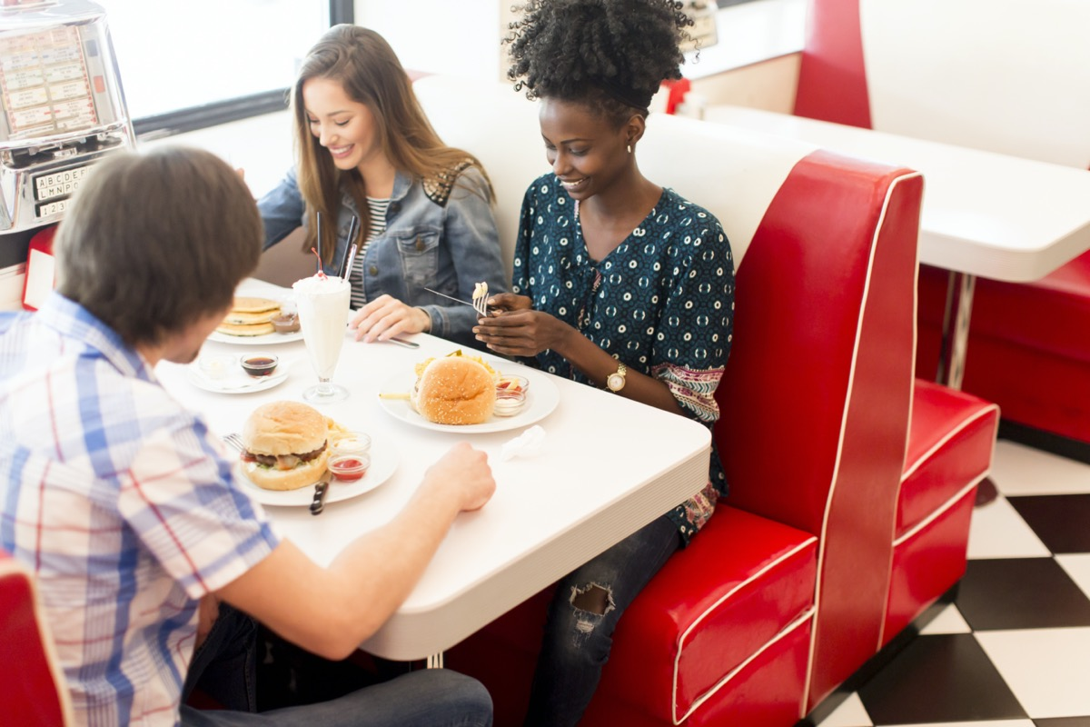young multiethnic friend group eating hamburgers at diner