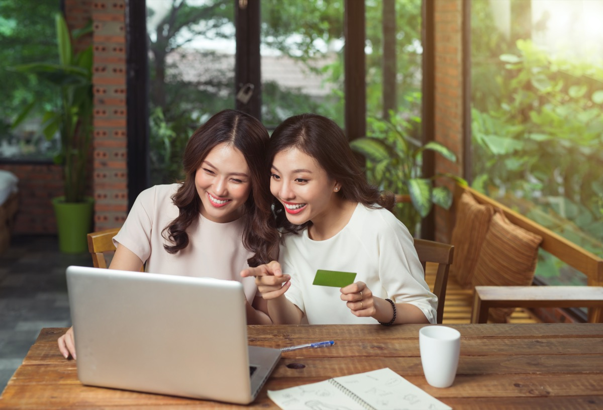 two Asian-Americans looking at pointing at something on a laptop and one of the girls holding a green card