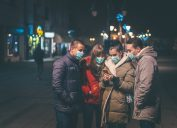 A group of young friends wearing face masks look at a smartphone in one of their hands.