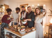 A group of young friends stand around a kitchen island during a small dinner party while taking a selfie
