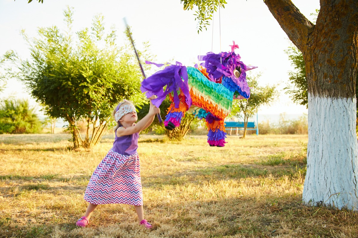 girl with blindfold hitting a multicolored piñata