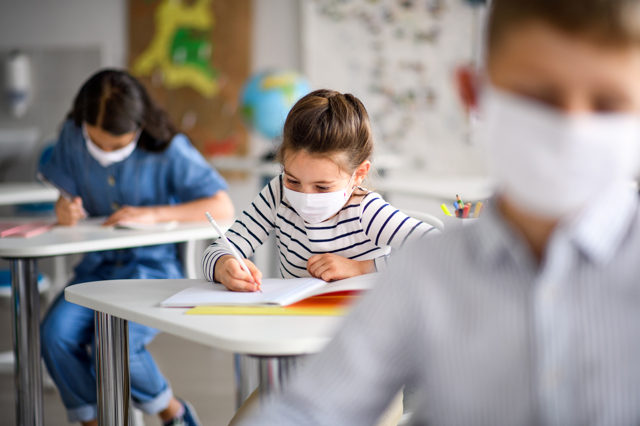 Children in a classroom wearing face masks and writing in notebooks.