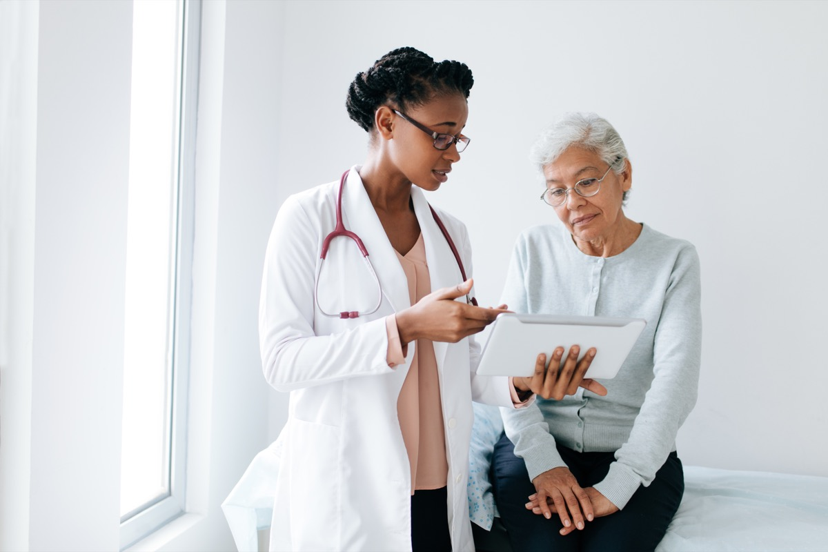 woman talking to young female doctor in glasses