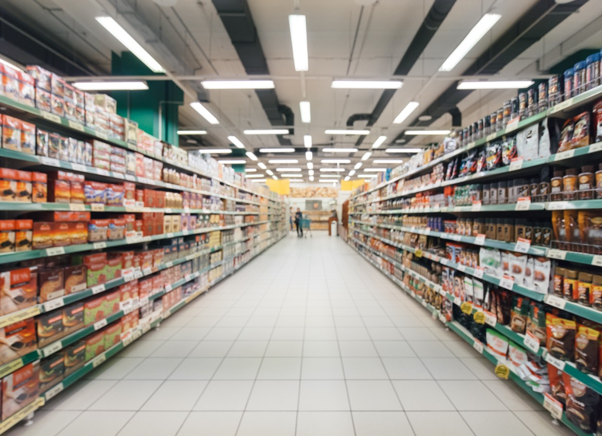 blurred, long, and empty aisle of supermarket with colorful shelves