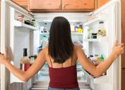 latinx woman in maroon tank top photographed from behind as she looks in the fridge