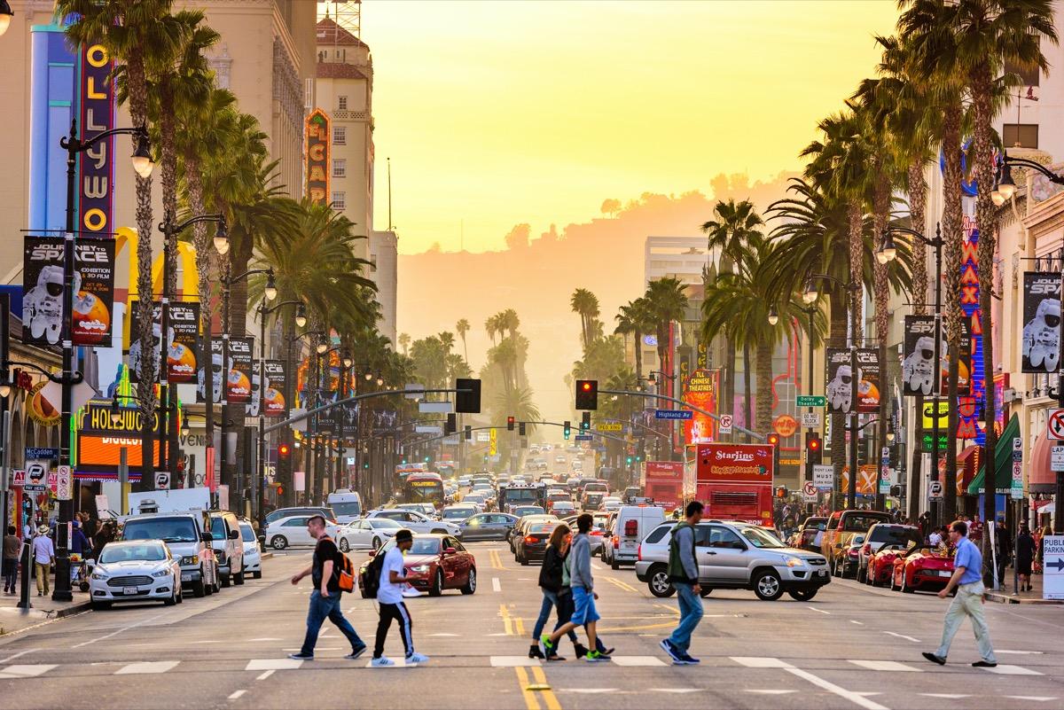 pedestrians walking across the street on Hollywood Boulevard in Los Angeles, California at dusk