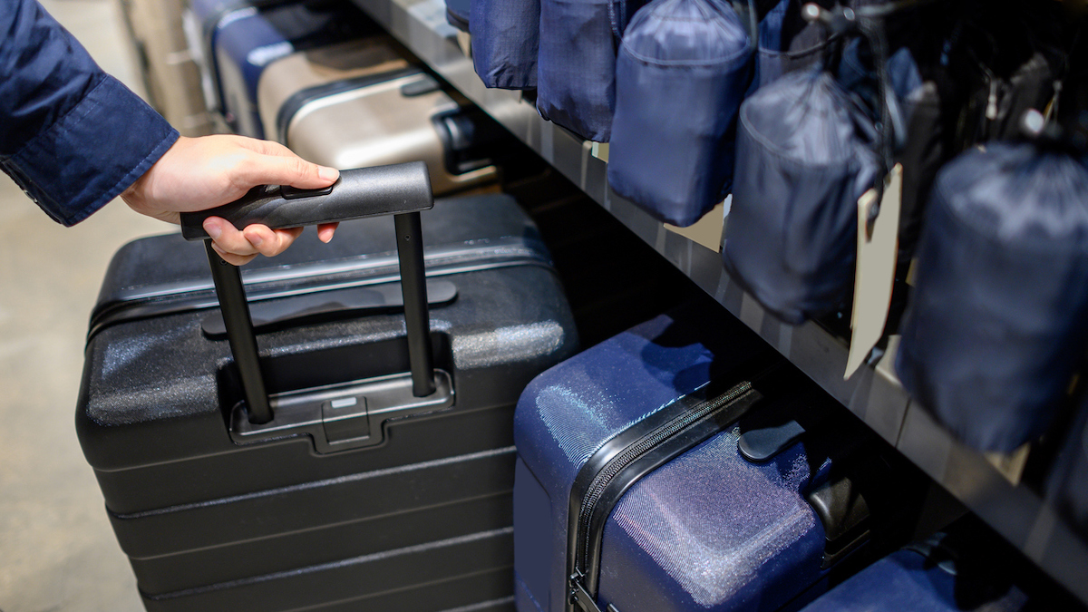 Male hand choosing suitcase luggage in the shop