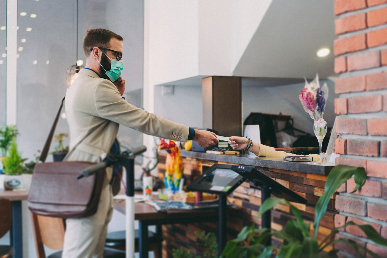 A man in a suit wearing a face mask hands over his credit card to a receptionist while checking into a hotel