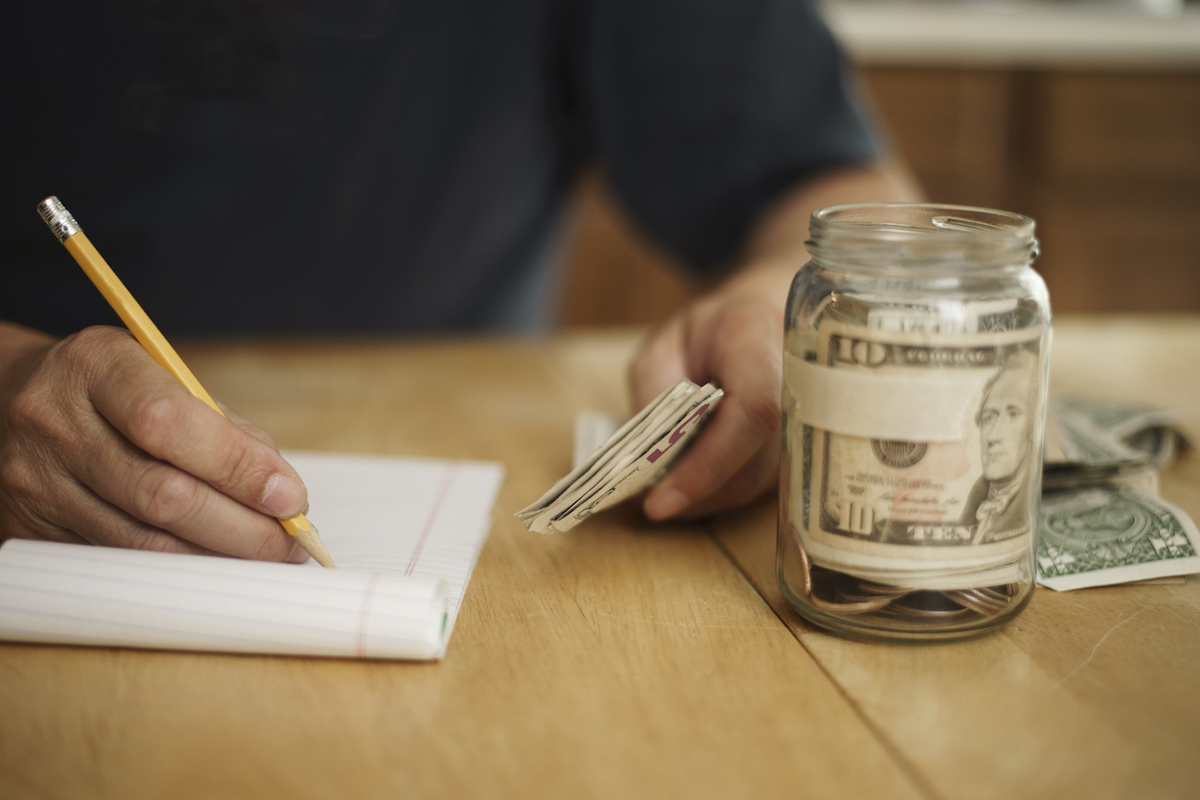 A male writes notes concerning money at the kitchen table. On the table is a pencil, pad of paper, paper currency and a jar fill with cash and coins.