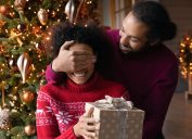young black man giving his wife a christmas present while covering her eyes