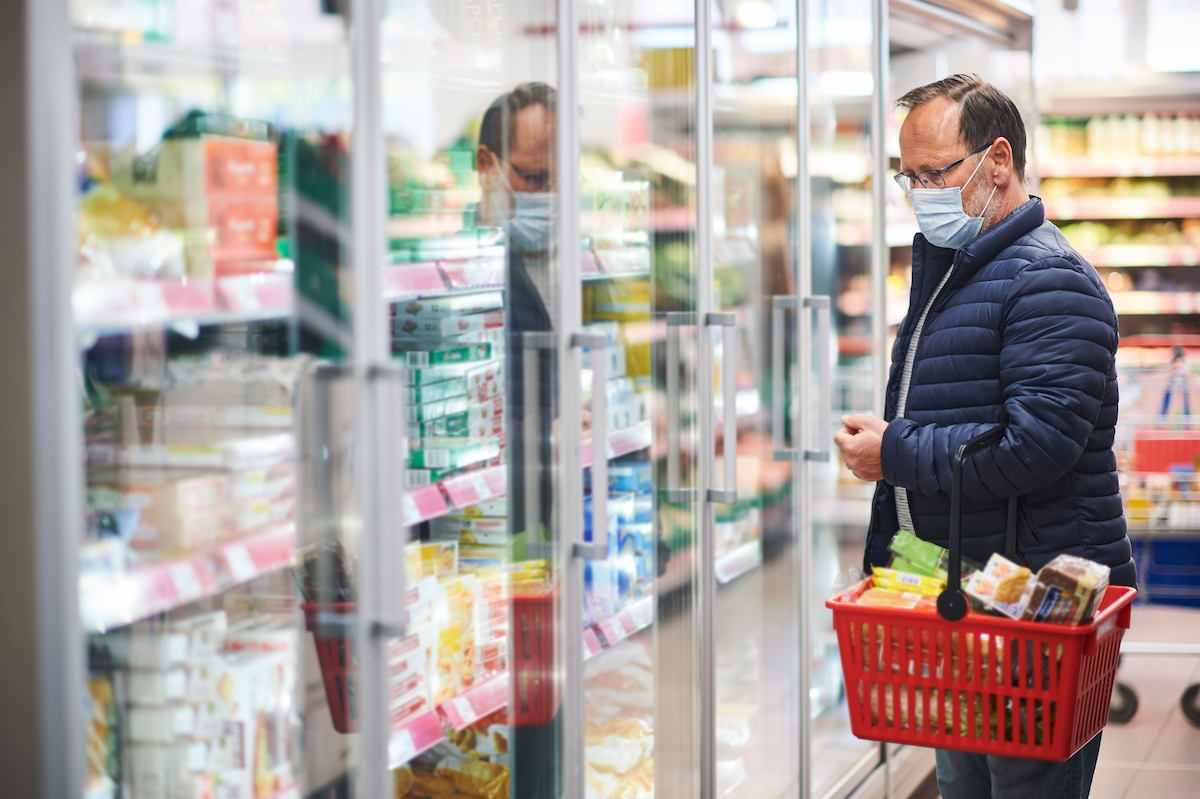 Middle age man buying food in grocery store, wearing medical mask