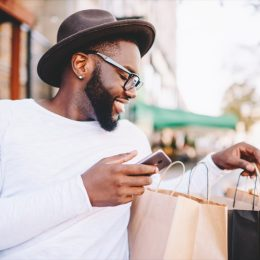 young black man looking at shopping bags looking happy