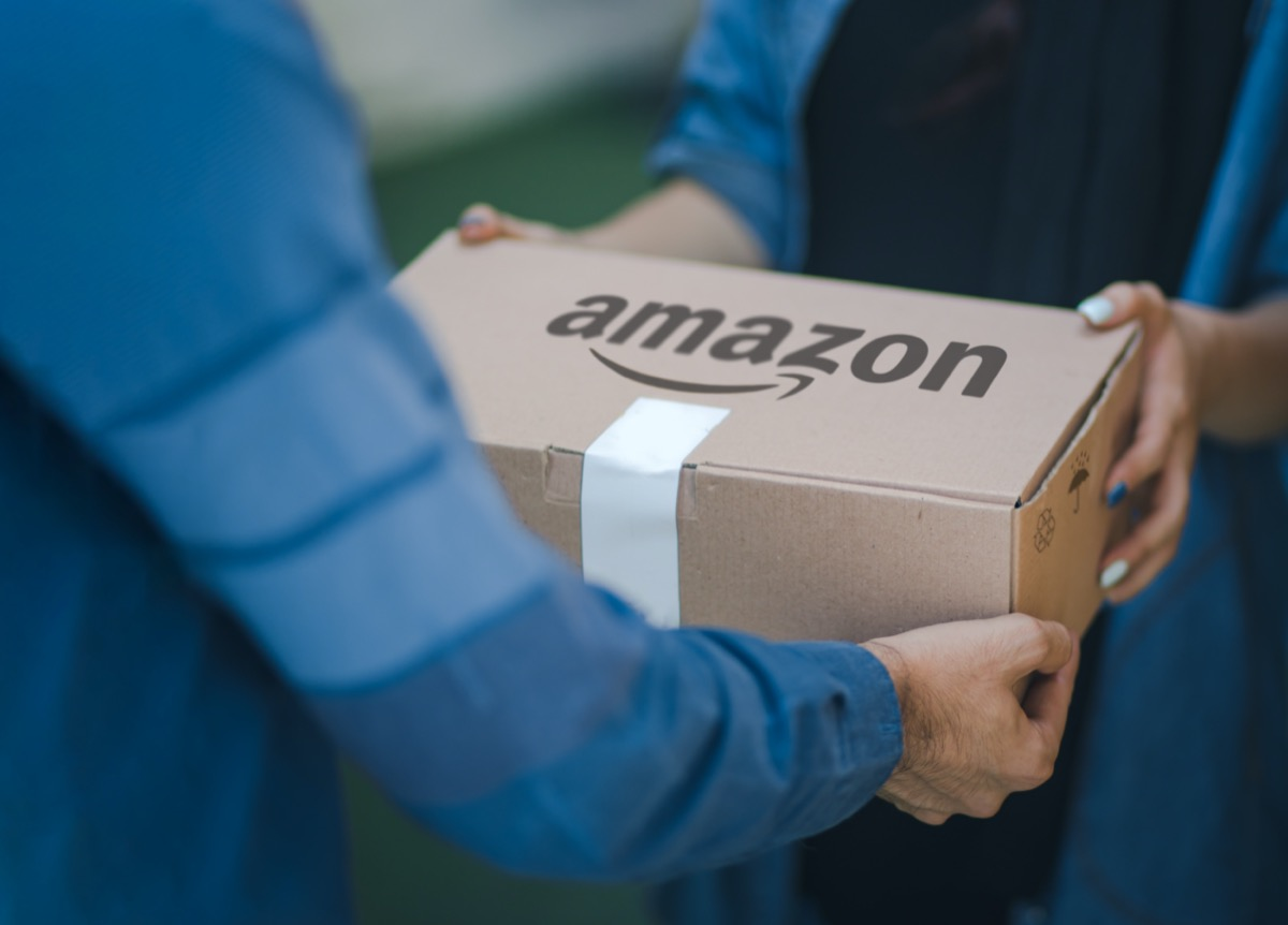 Malaga/Spain - 10-09-2020 : selective focus on man delivering parcel with amazon logo on cardboard