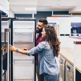 man and woman shopping for fridges