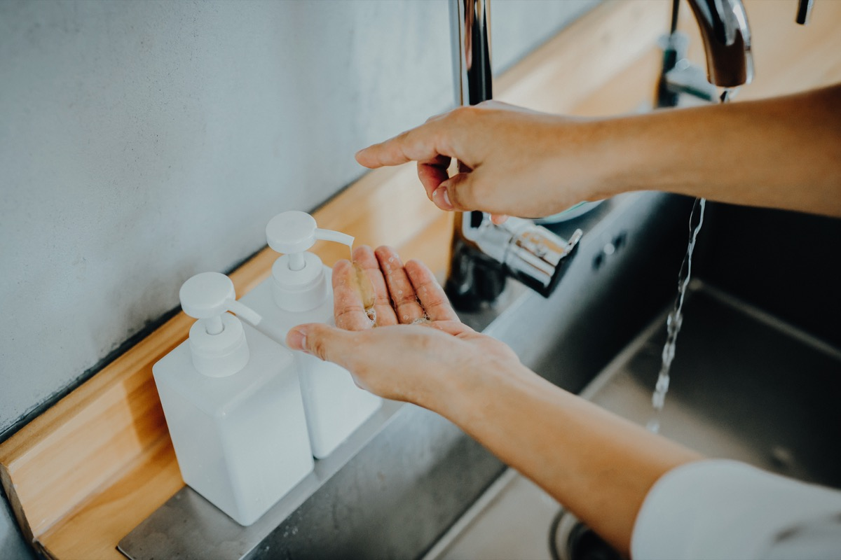 Cropped shot of a man dispensing soap before washing his hands in the sink
