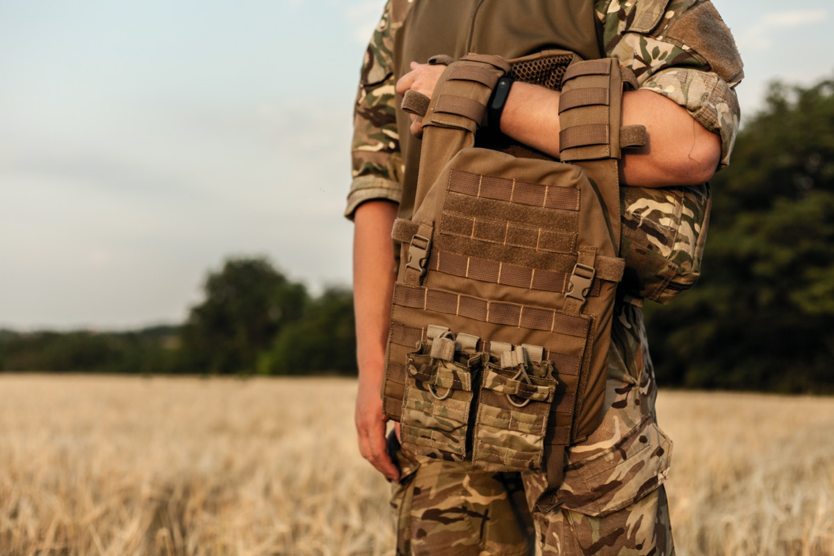 military man standing in the filed in his outfit and with a bulletproof vest