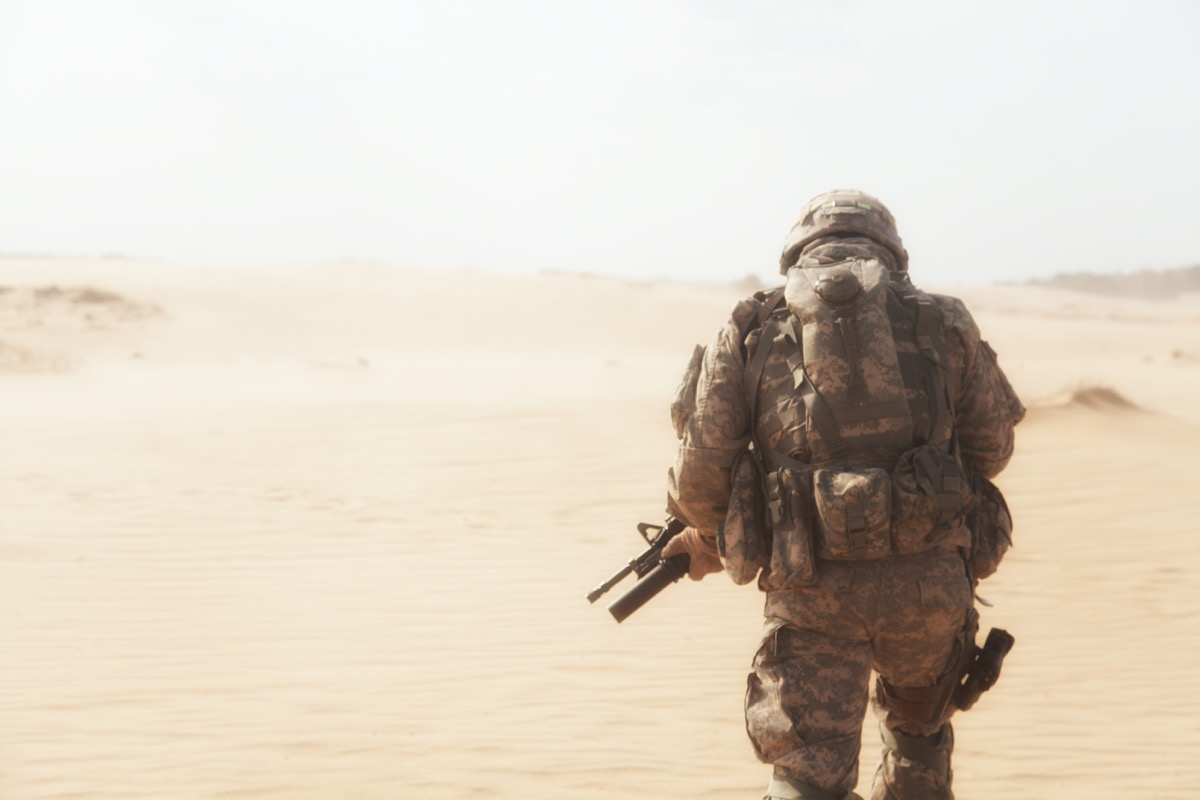 military man from behind heading into a desert