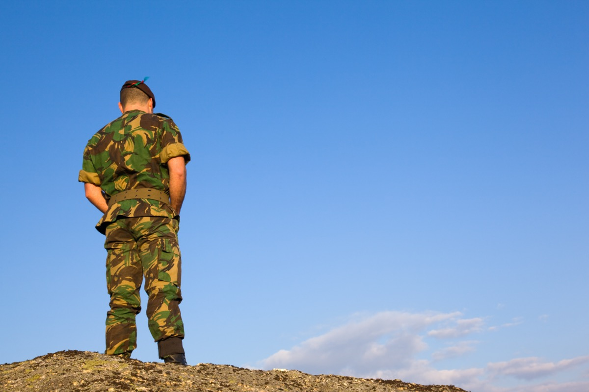 the back of a military man standing and looking down