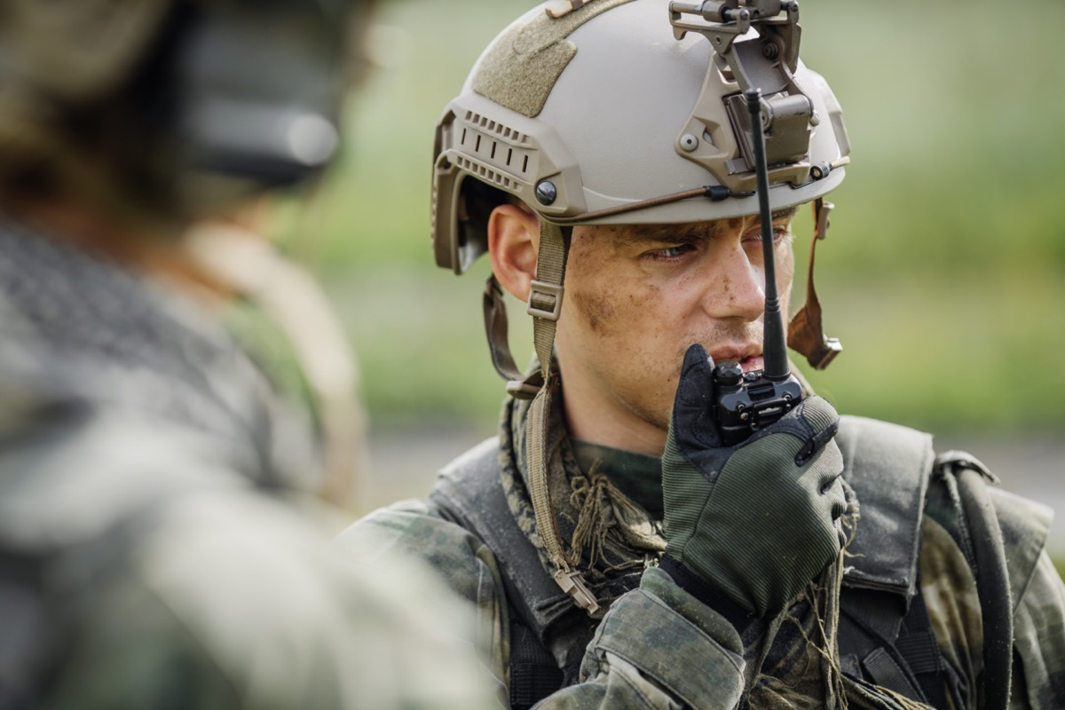military officer talking into a walkie-talkie