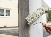 painter using roller to paint column on home's exterior
