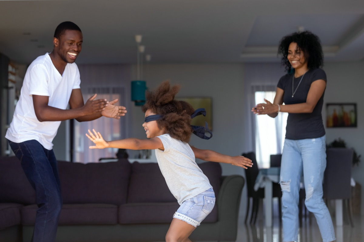 African-American parents play marco polo with their daughter wearing blindfold