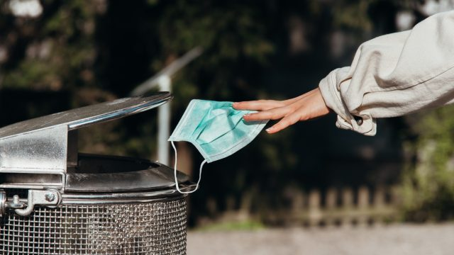 A person throwing away a face mask into a garbage can.