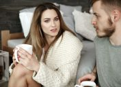 Couple with coffee arguing at bedroom