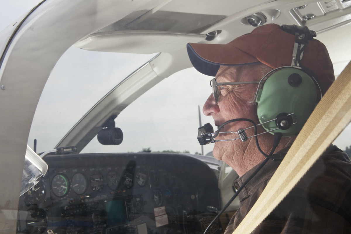 veteran in and flying a plane with blue headphones