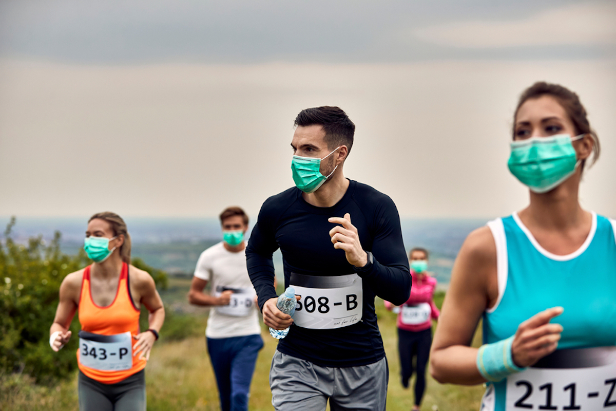 Group of runners wearing protective face masks while participating in a race during virus epidemic