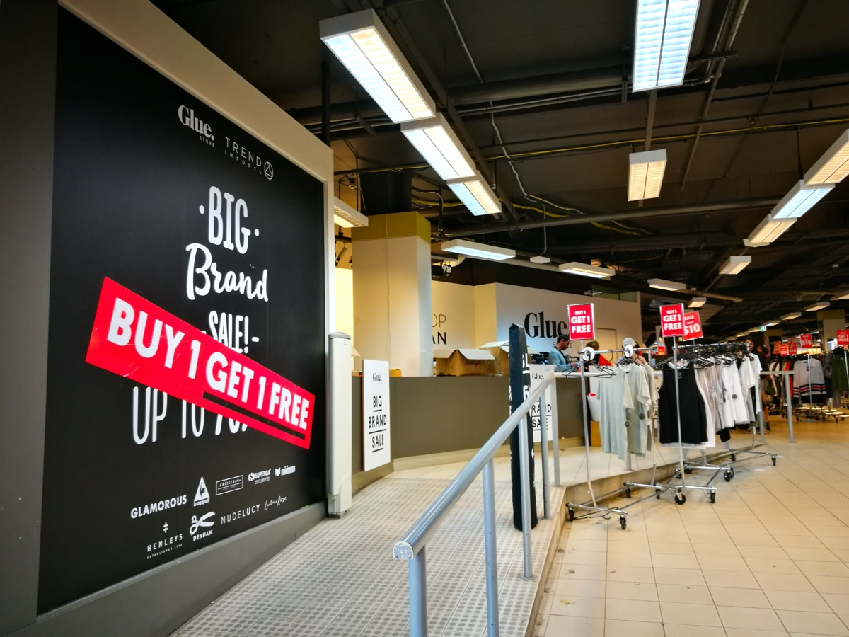 'Buy 1 Get 1 Free' Sign on wall of store and rack of clothes on sale